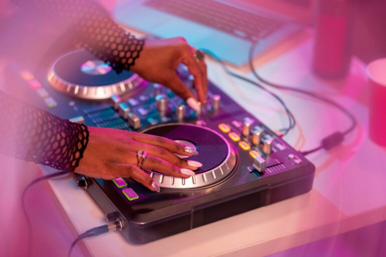 Hands of African female deejay moving turntable and mixing sounds