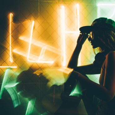 Hip-hop girl in cap in neon light. Fashion portrait of modern young woman in cap.